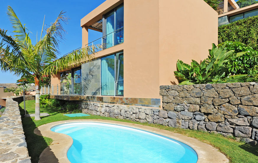 Bright villa with large glass windows, outdoor relaxation area, heatable private pool and view towards the golf course
