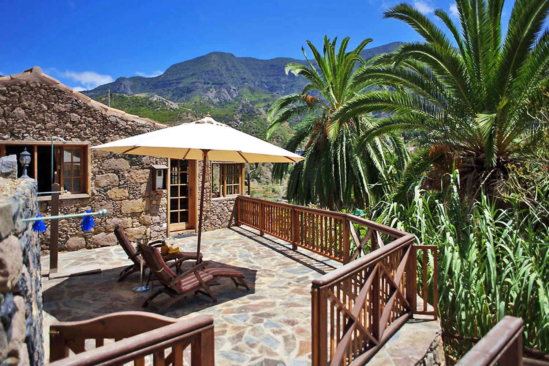 Mooi landhuis uit steen en hout, gelegen in een vallei vol palmbomen en met prachtig uitzicht op de groene bergen